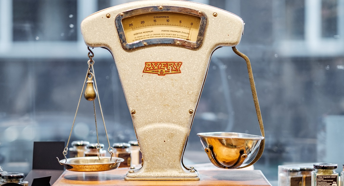 A metal, antique scale sits level on a desk.