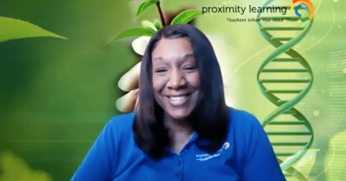 A teacher smiles while teaching virtual science class.