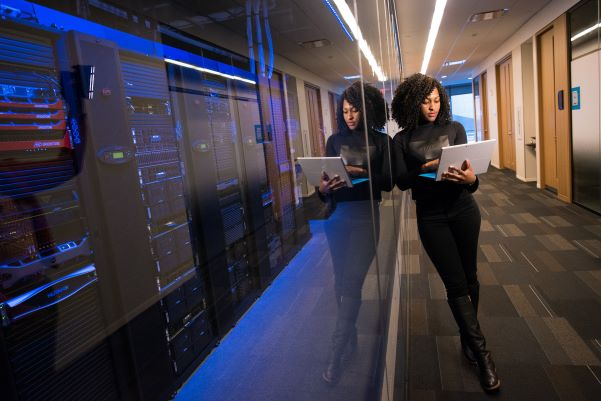 Woman leaning agaist a tack of servers in a server room