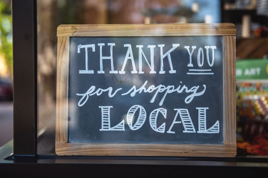 Chalkboard in cafe saying 'thank you for shopping local'