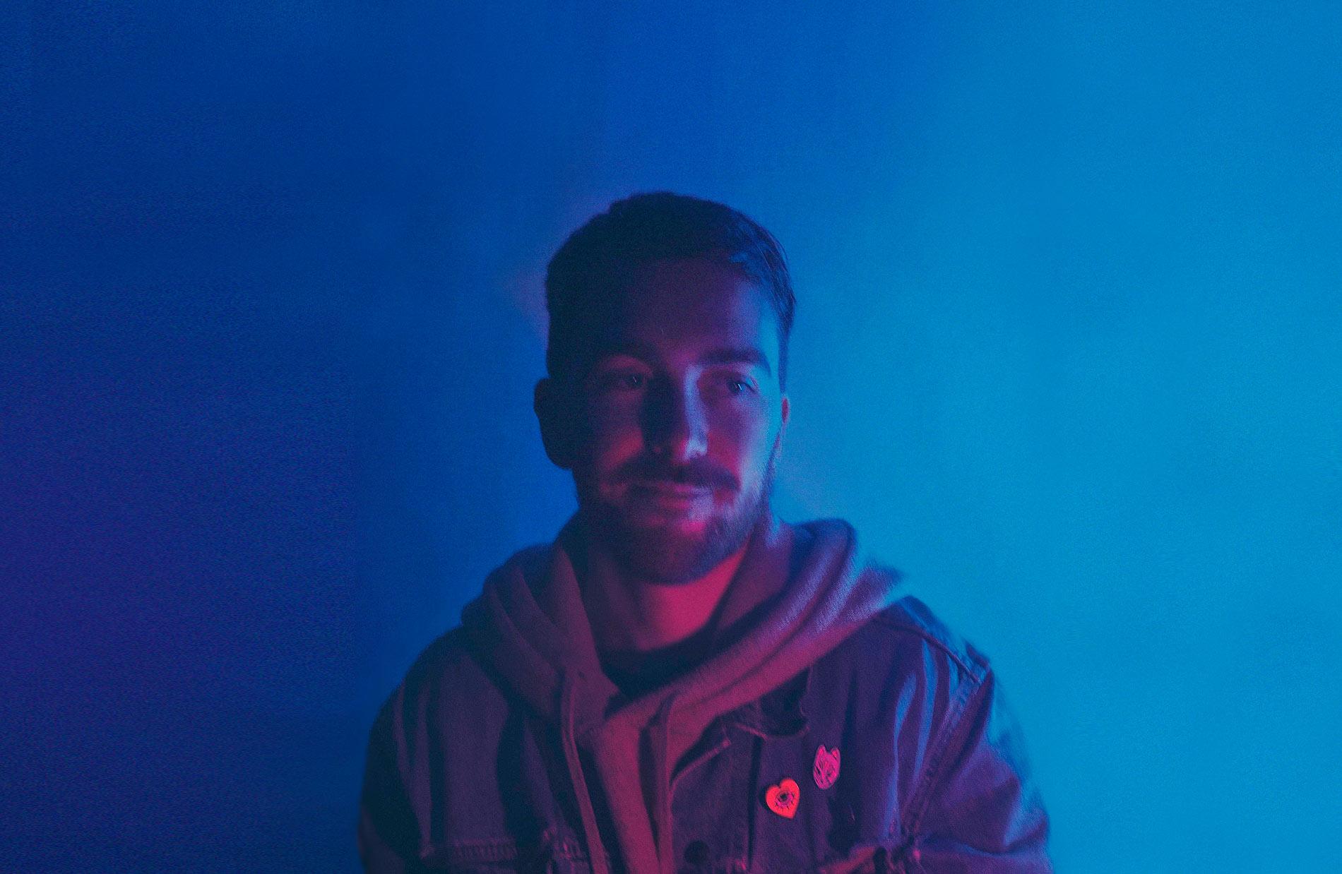 Portrait of Florian Pollet under blue neon lights