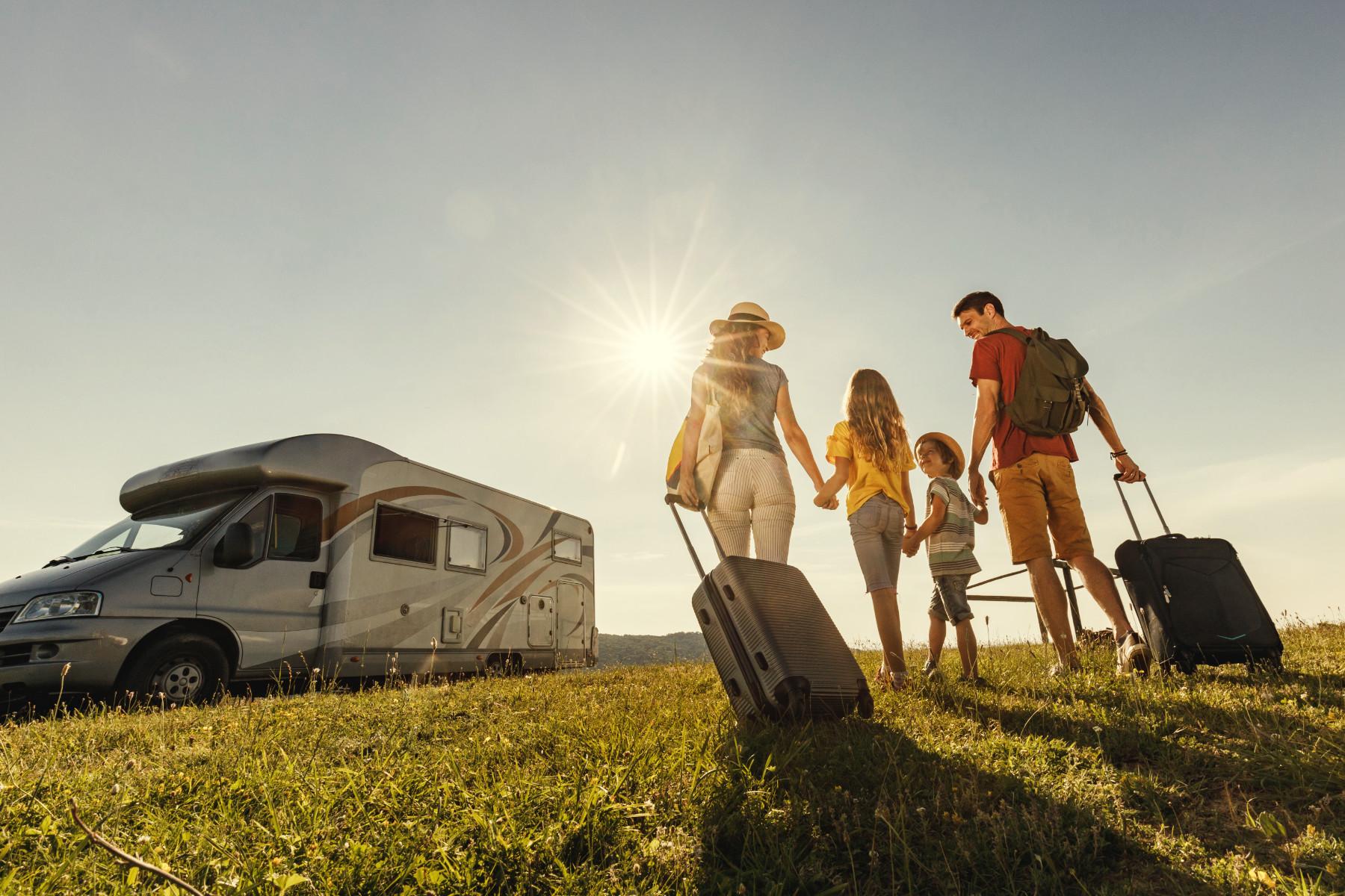 Familie mit Reisegepäck und Wohnmobil im Hintergrund