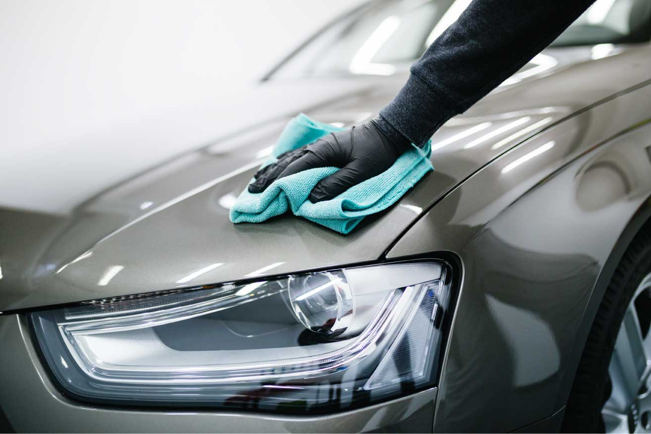 hand cleaning car with towel
