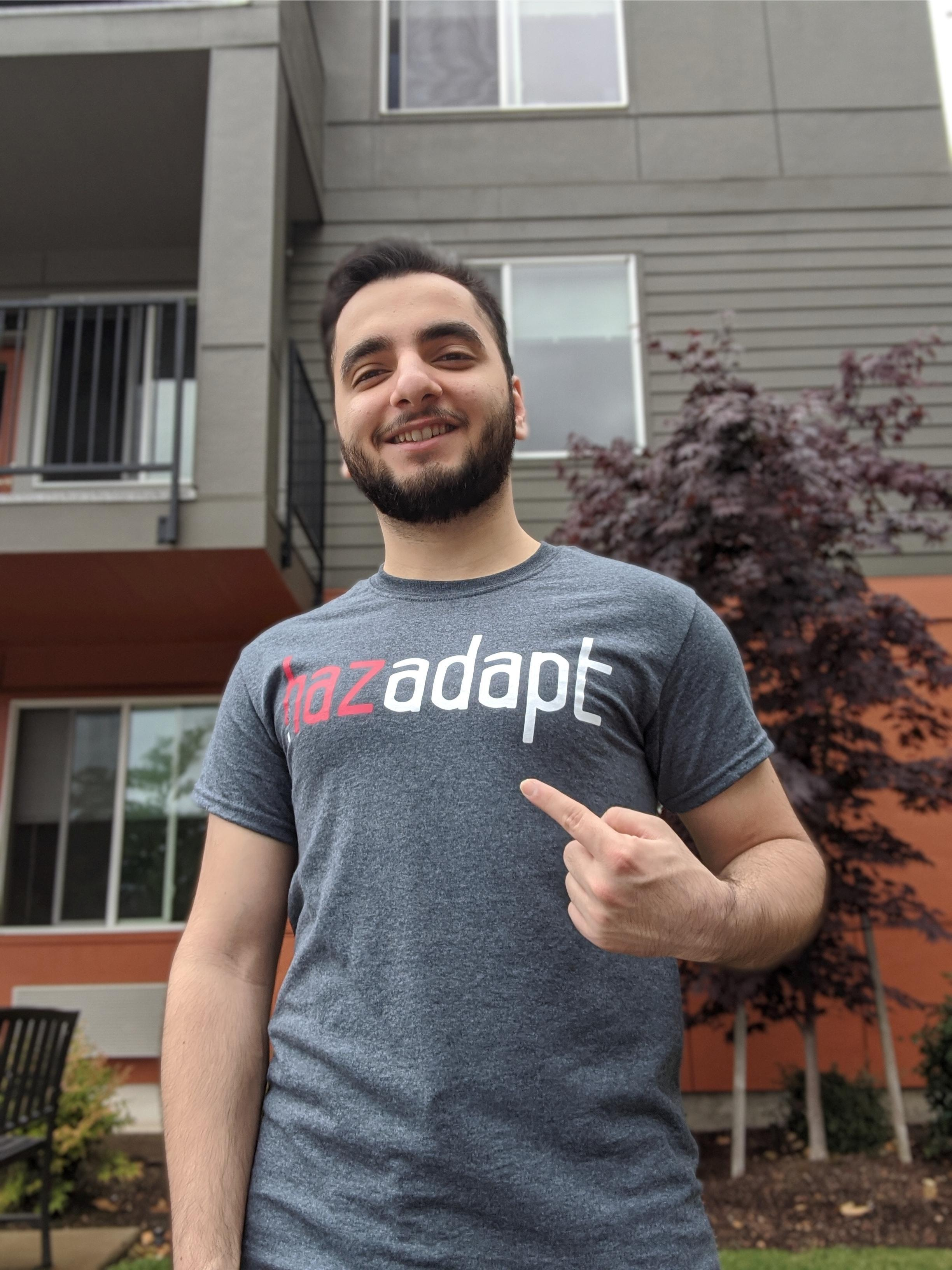 A HazAdapt team member pointing to his HazAdapt t-shirt.