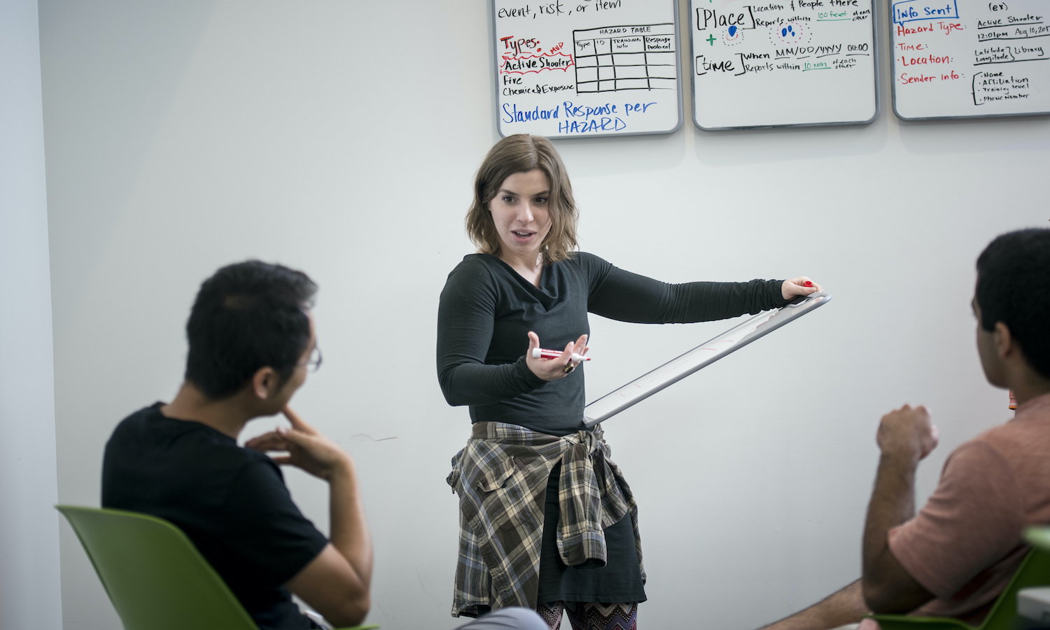 HazAdapt Founder and CEO Ginny working on a whiteboard with teammates.