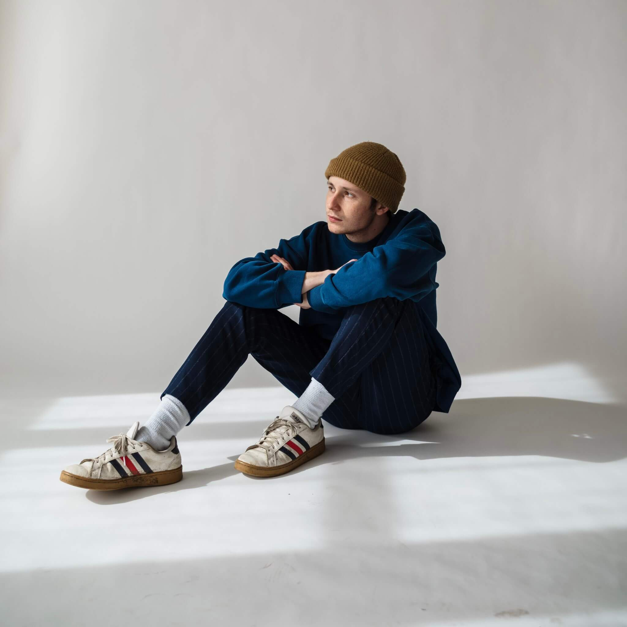 man sitting on the floor with beanie