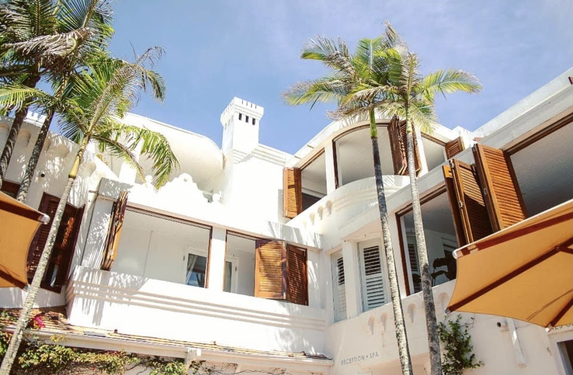 Raes on Wategos (white triple-story hotel) surrounded by palm trees in front of a blue sky