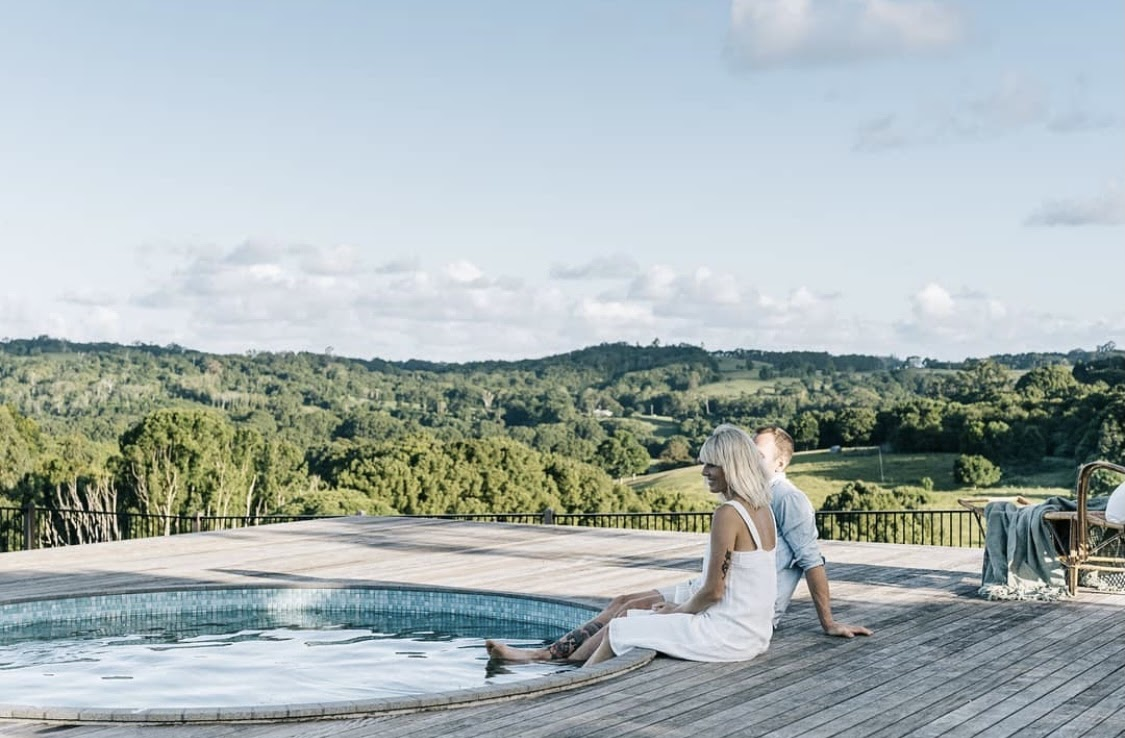 A couple dipping their feet in Heartwood Farm's circular pool while facing farms and meadows