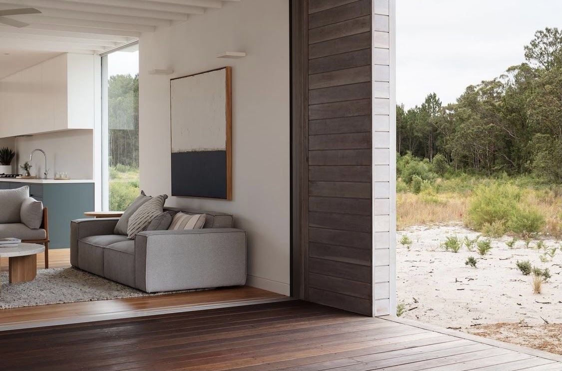 Living area of the Courtyard House which features a grey couch, minimalistic design and extends directly into the rugged outdoor landscape