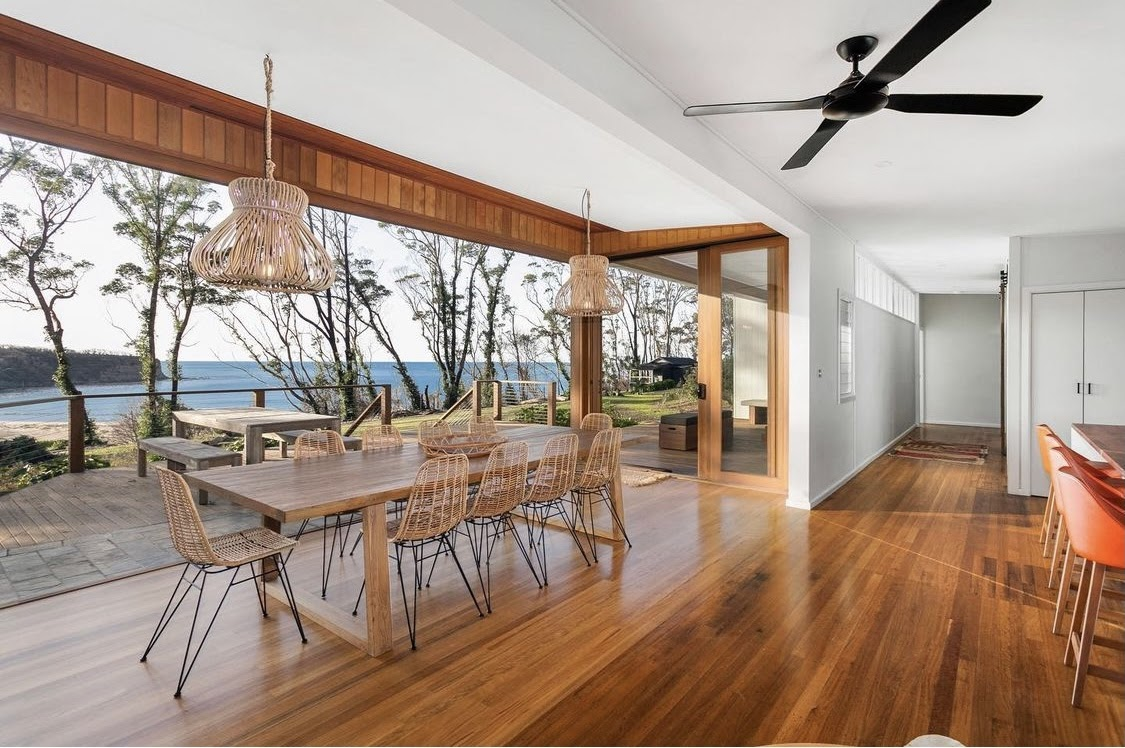Dining space of Pebbly Beach Escape which features wooden furniture and connects directly to the outdoor beach