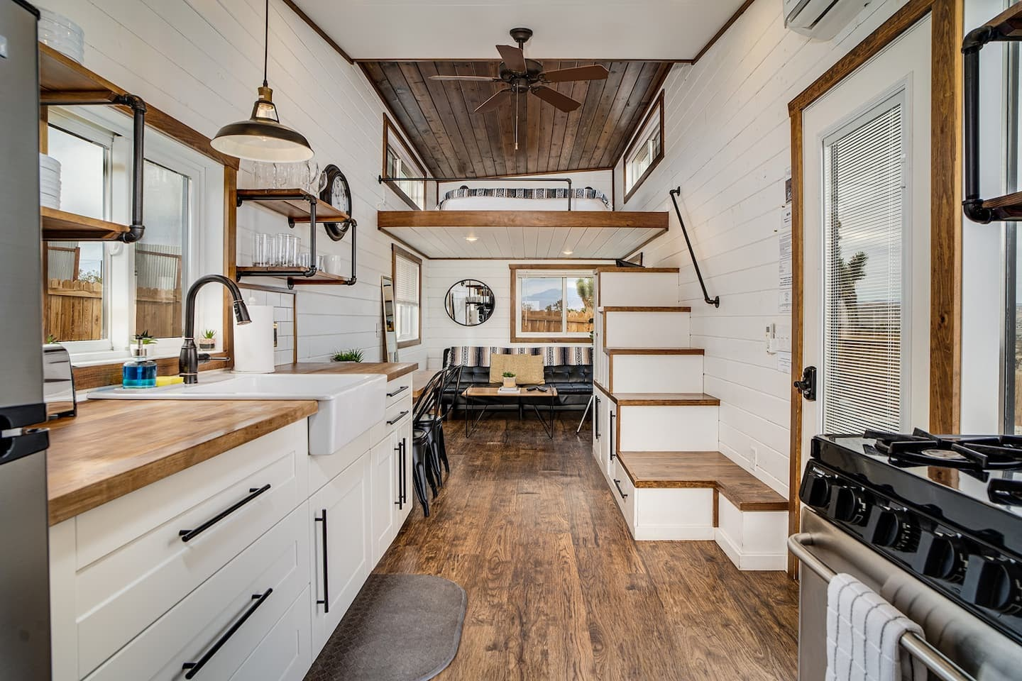 Interior of The Little Dipper with an open living area, contemporary kitchen and floating platform with a Queen bed