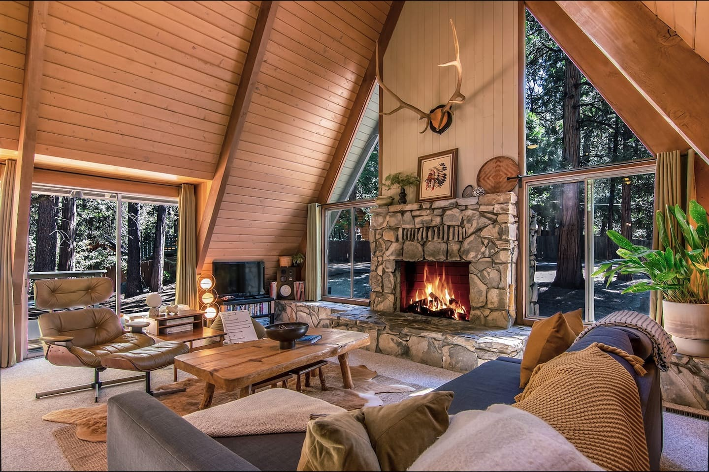 Main living area of The Far Out featuring a slate stone fireplace, grey couch, deer sculpture and wooden walls