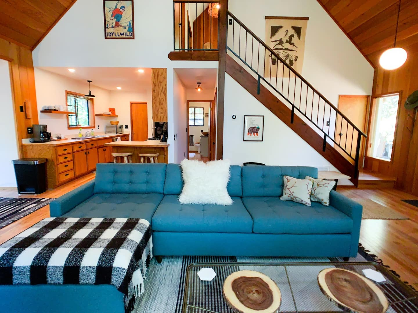 Main living and dining area of Black Pine Cove with a blue couch, high-rise ceilings and wooden furnishings