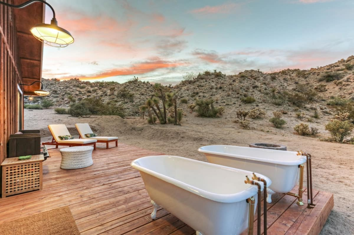 Deck of La Luna Cabin which features twin bathtubs, two reclining seats and faces the Californian high desert