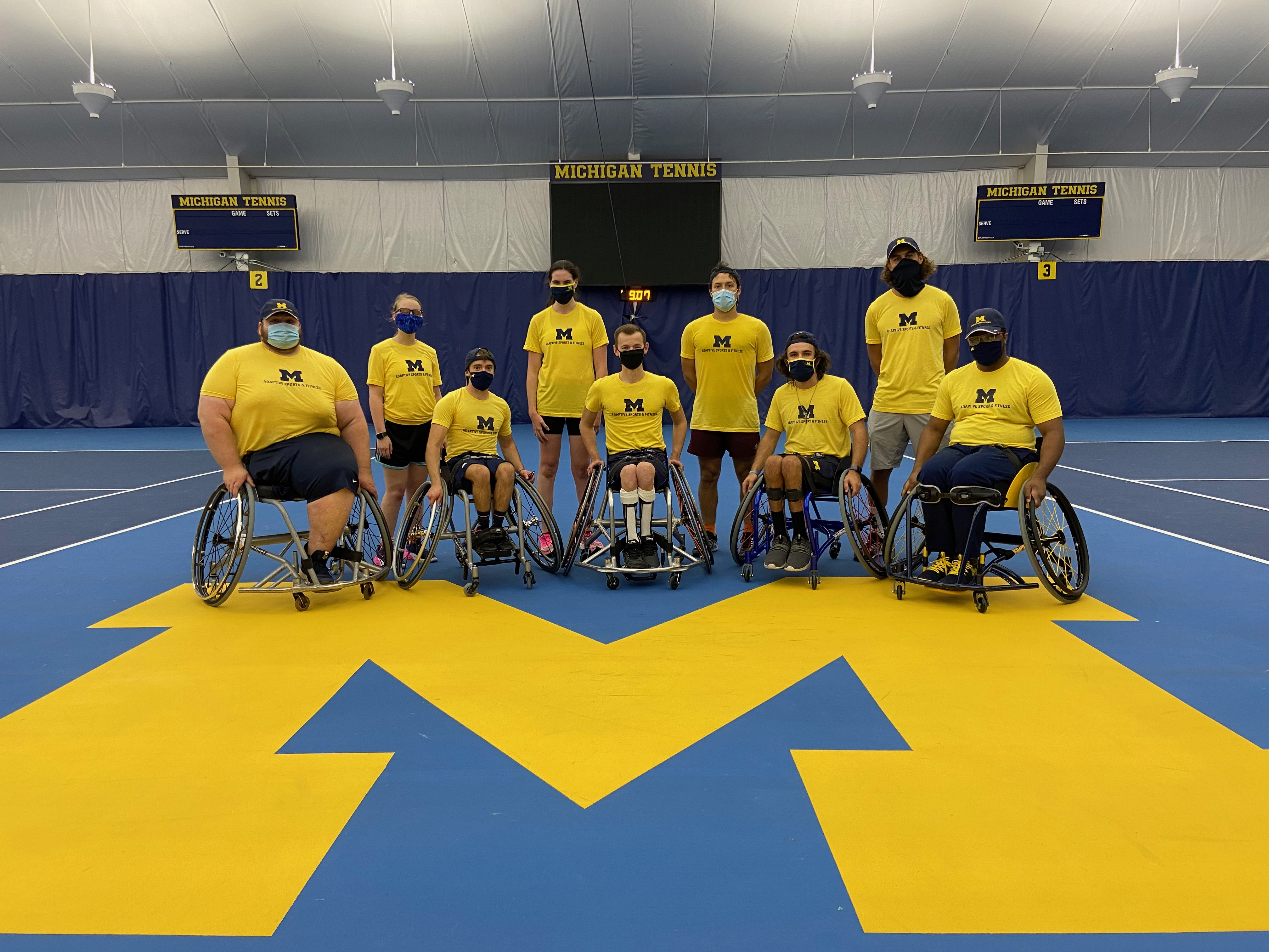 Image of team wearing matching maize program shirts on the tennis court