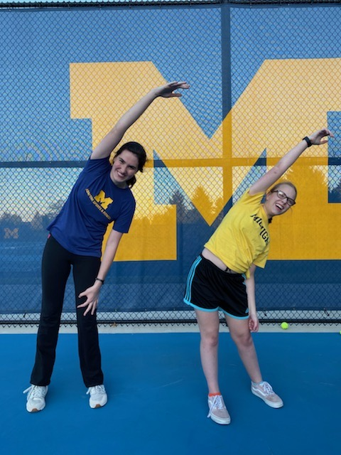 Two track athletes demonstrate a horizontal standing stretch