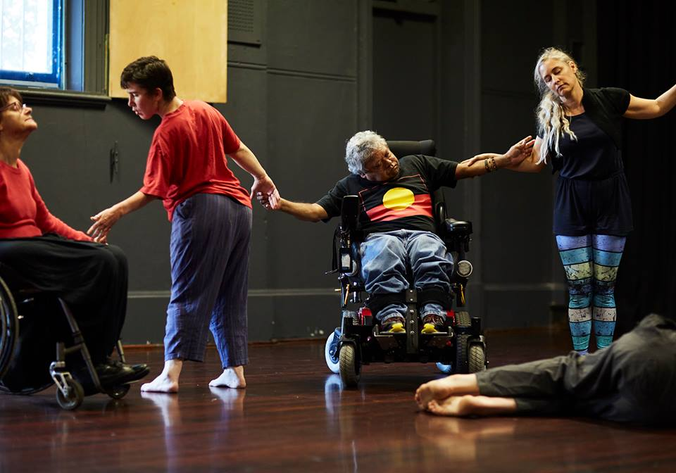 Four people, two in wheelchairs making a chain in a line by touch arms or hands with eyes closed in rehearsal space with wooden floors.
