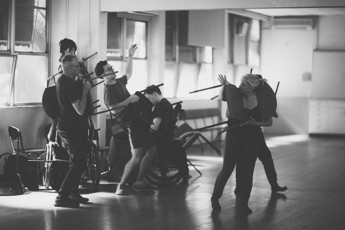 People moving with chairs, holding them in different ways in rehearsal space.