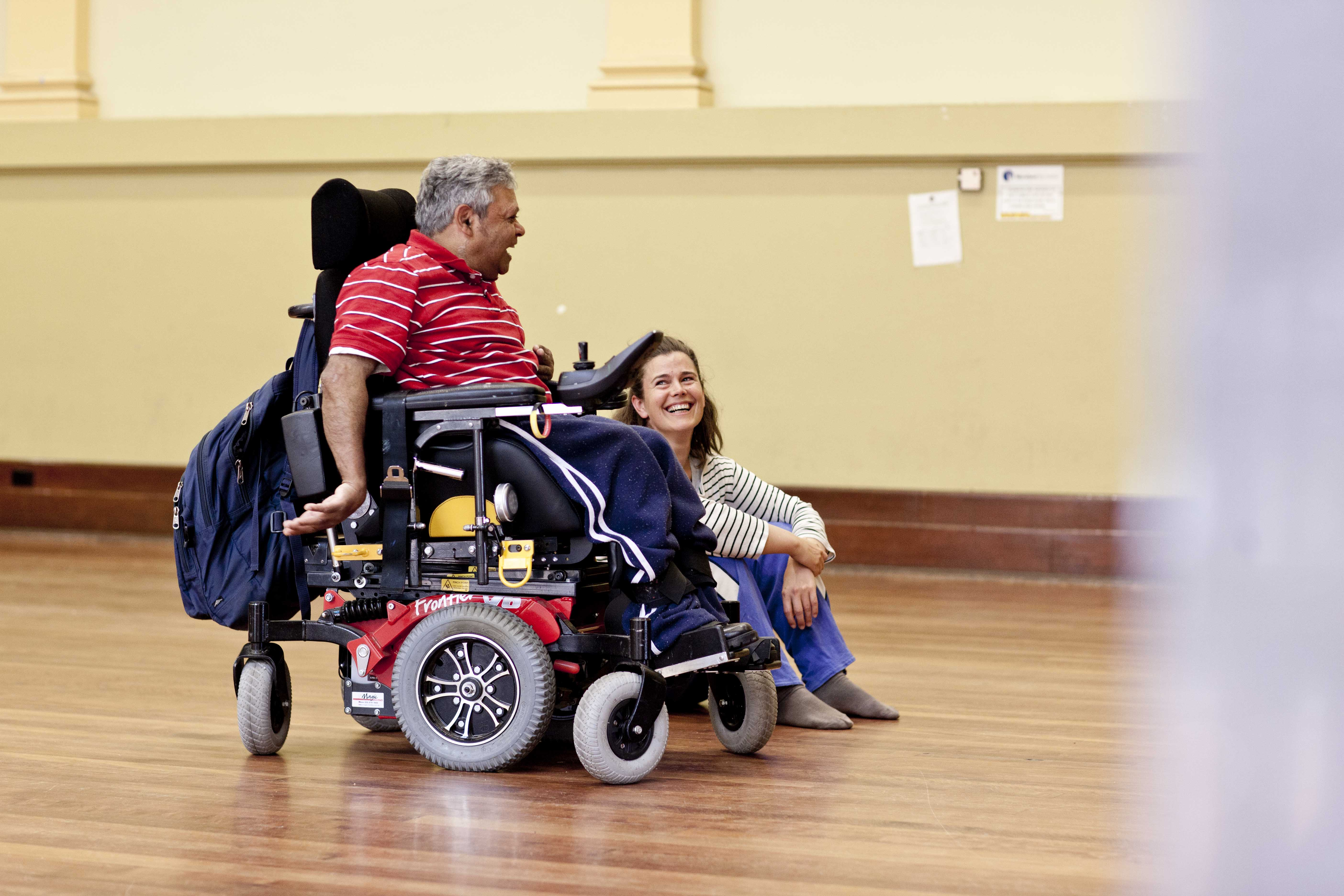 Man in wheelchair laughing with woman sitting on the floor.