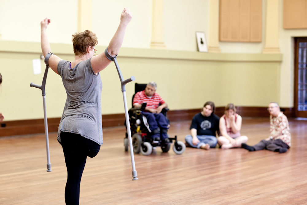 Woman with one leg holding up arms in strong proud motion with crutches with a small group of people sitting watching.