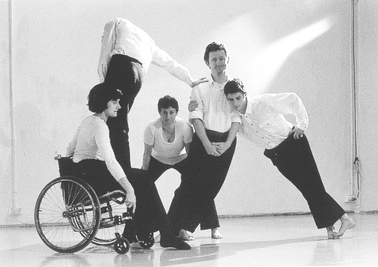 Five people in black and white holding different positions, leaning on one another, one woman is in a wheelchair.