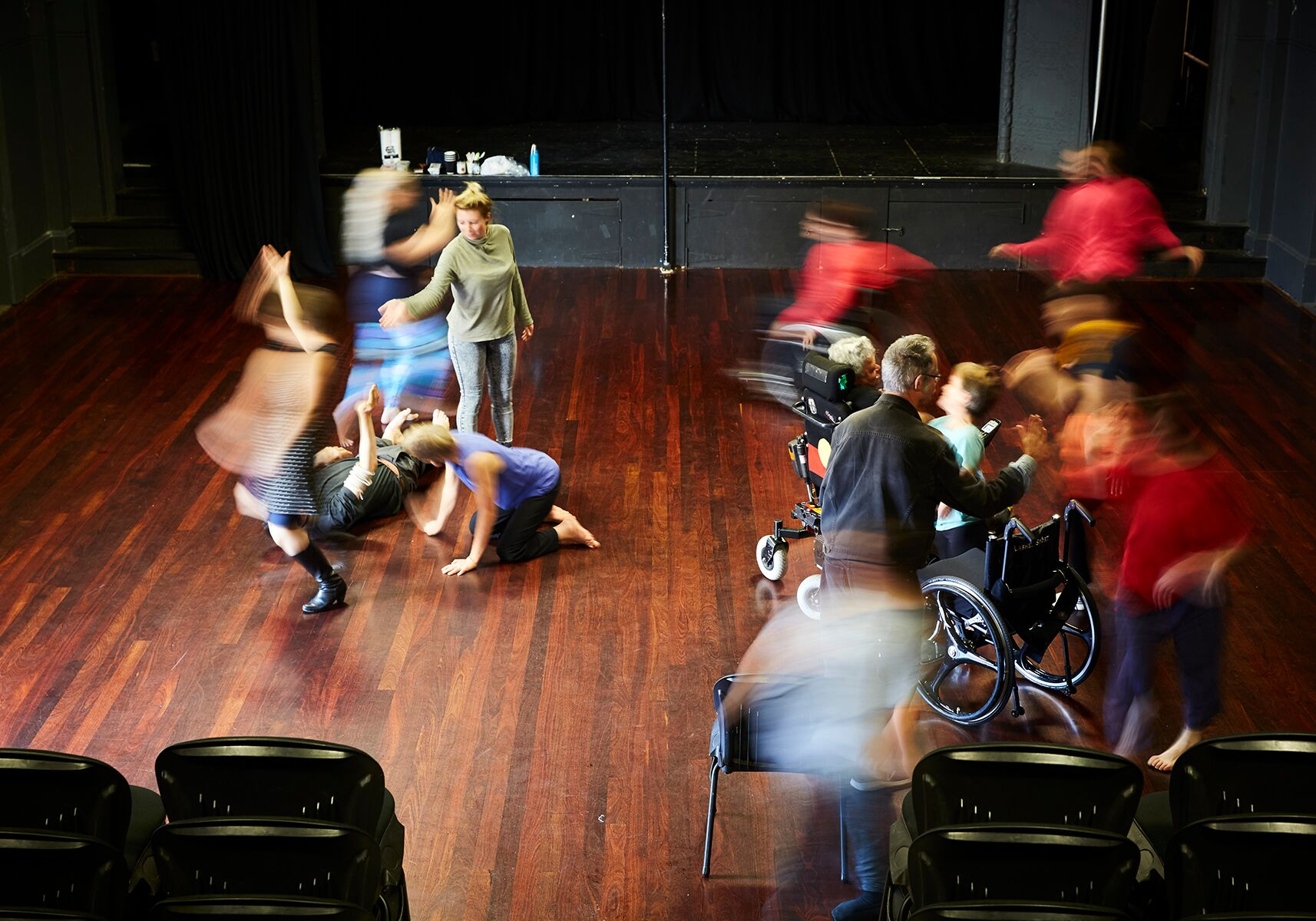 Group of people moving in rehearsal space with wooden floors.