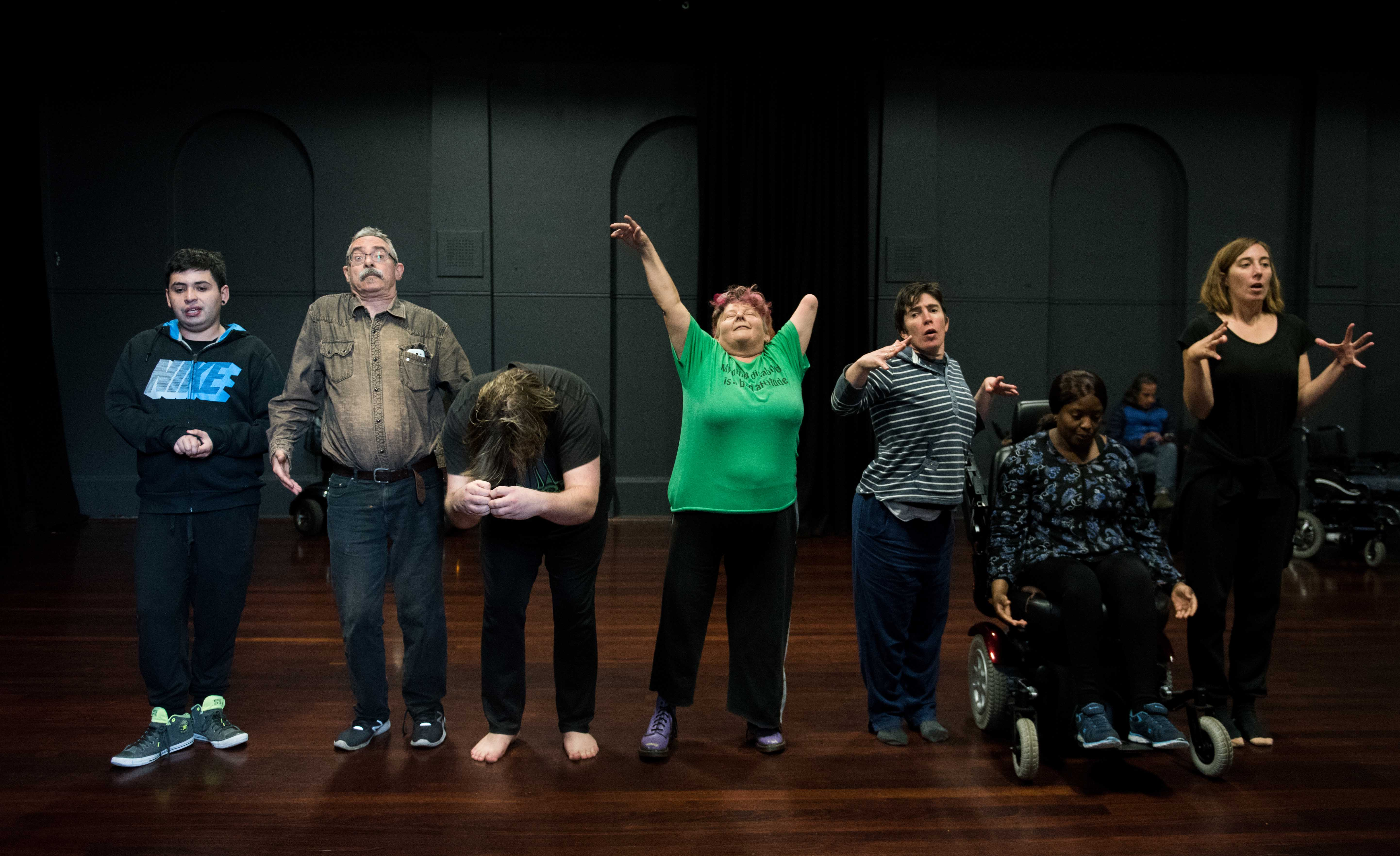 Seven people of different ages, genders and nationalities stand straight out to the camera in a row holding different positions with their body.