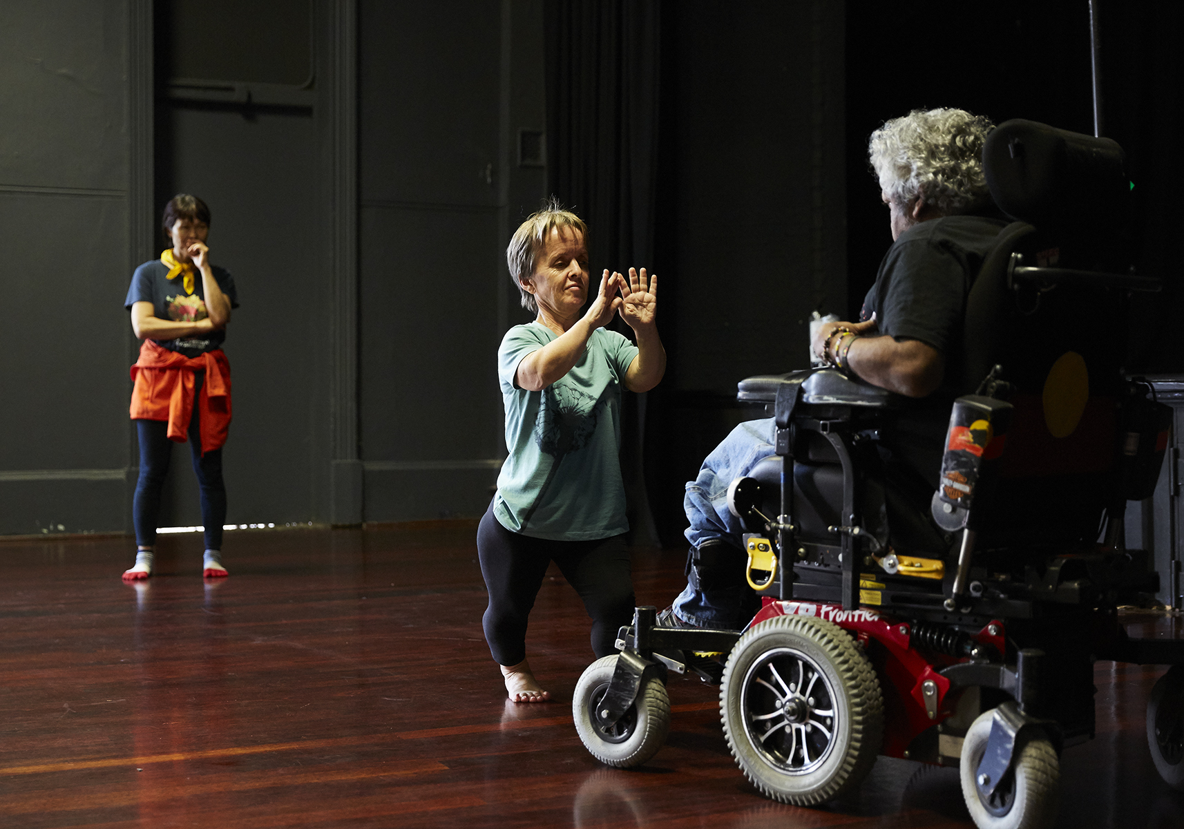 One woman holds out hands with palms flat to person sitting in wheelchair whilst one woman stands watching.