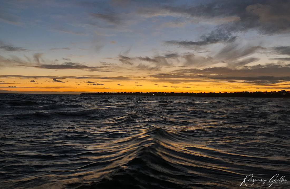 Dark ocean waves of Port Philip Bay off Parkdale beach. In the distance, an orange sky as the sun disappears over the horizon