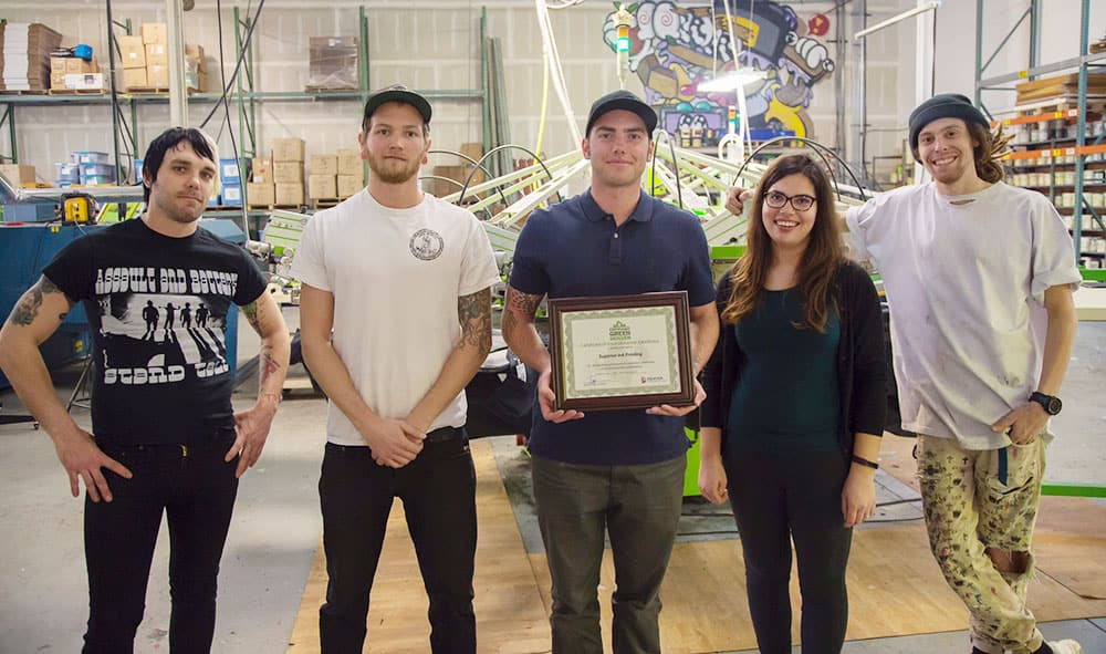 Screen printing team proudly showing sustainability award