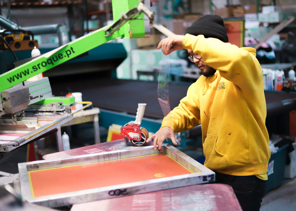 Man running screen printing press