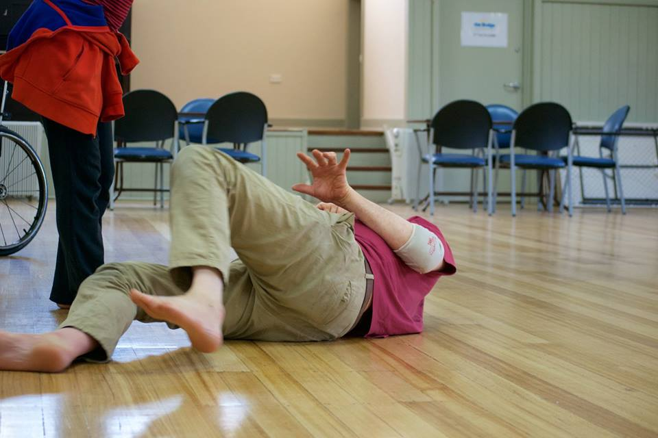 Man lying on a wooden floor with feet towards the camera, wearing beige pants and red t-shirt in rehearsal space.