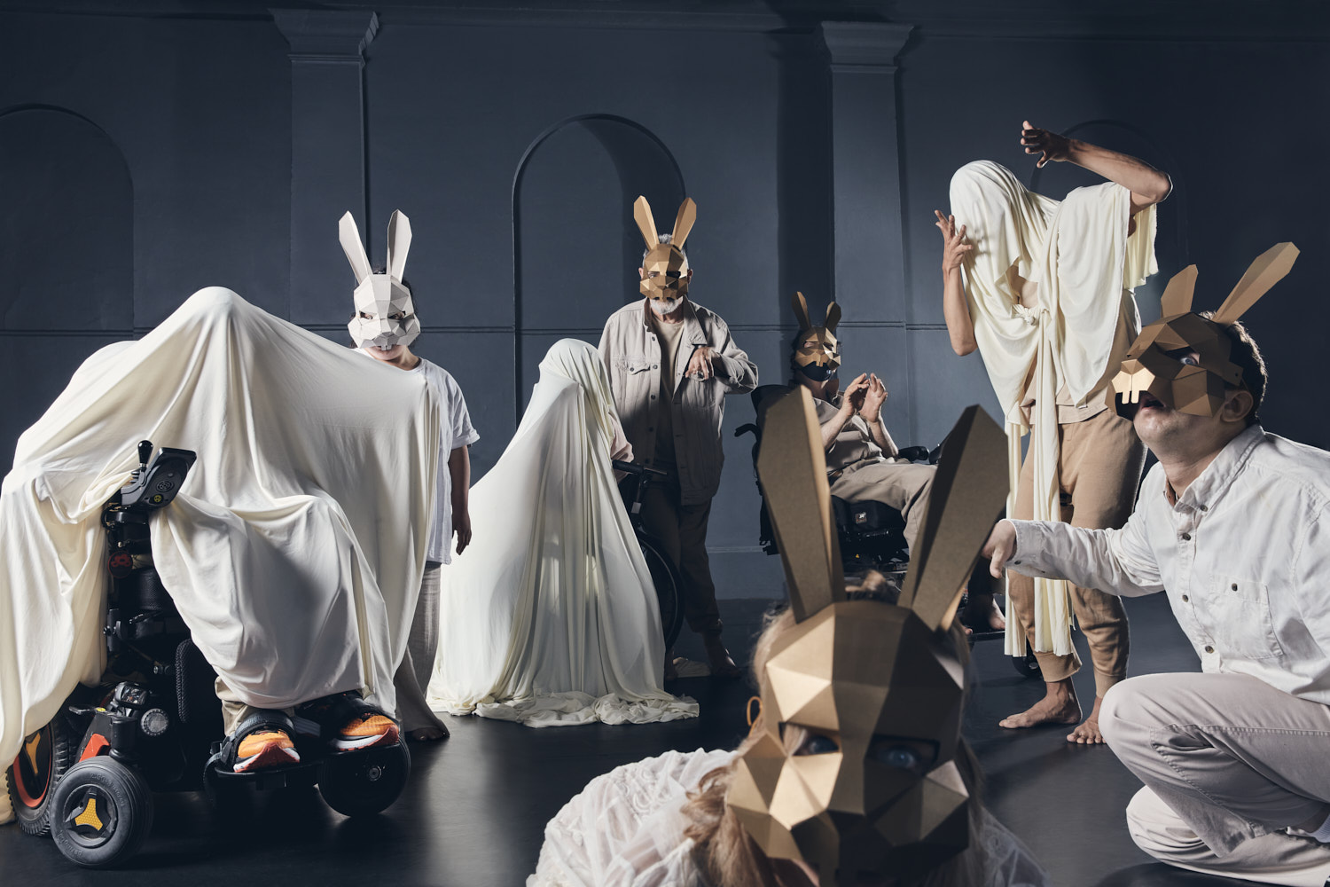 Group of performers dressed in white and cream holding different positions, staggered close to far away from the camera. Some people have sheets wrapped around their head and body, others are wearing gold geometric rabbit masks.