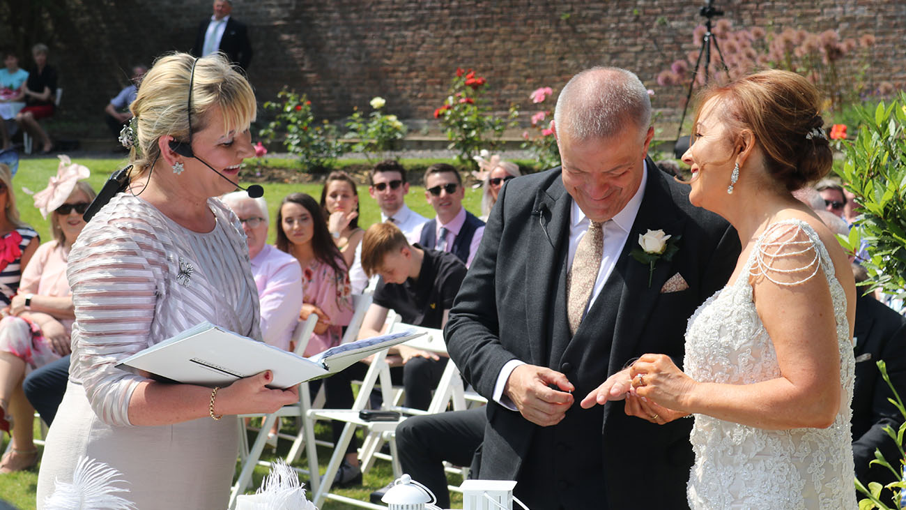 Reverend Lorraine McCarthy with Groom and Bride in an Outdoor Ceremony