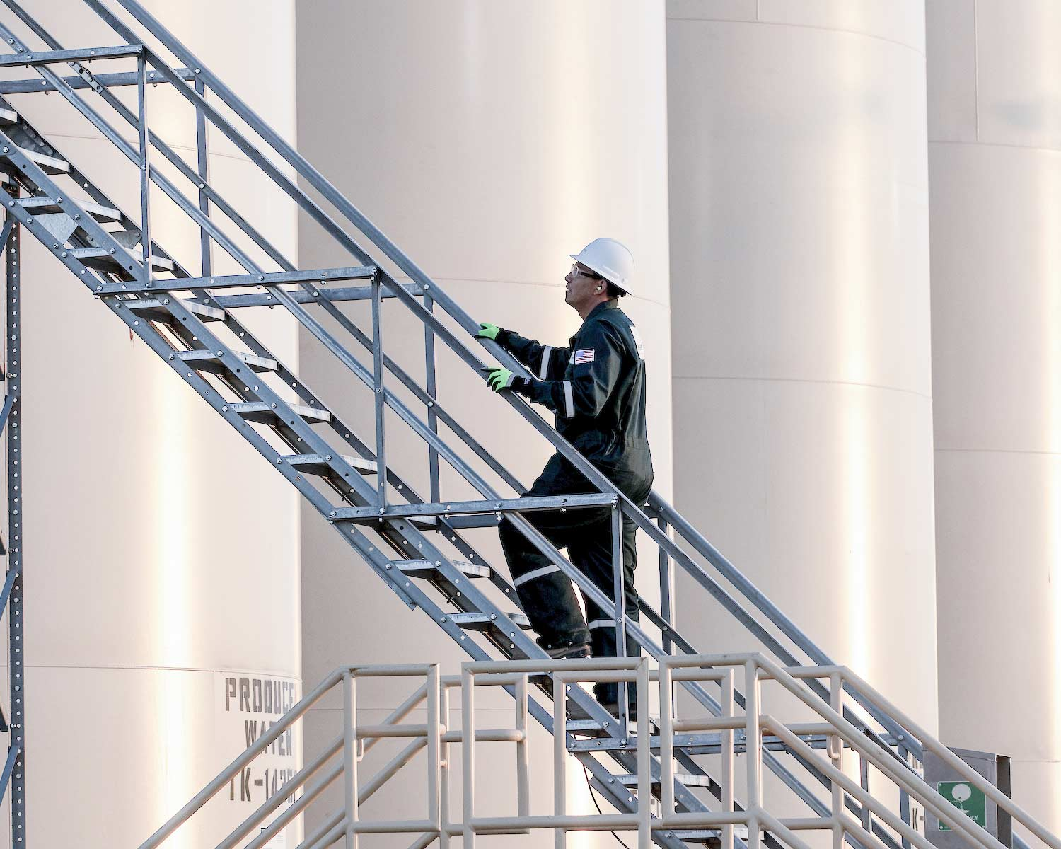 A worker climbs a set of stairs on an industrial worksite, protected by shepherd safety systems gas detection technology