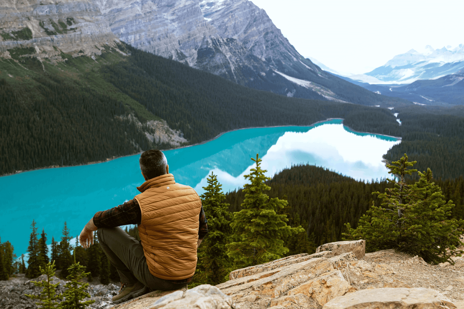 Man sitting on cliff over looking a beautiful river