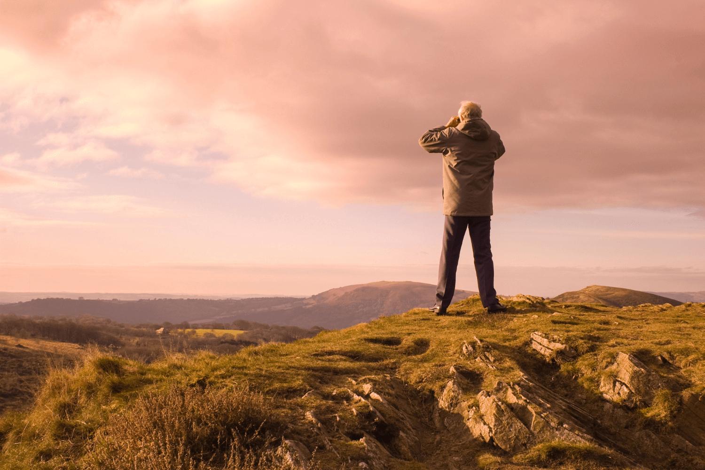 Man looking through binoculars while standing on a mountain