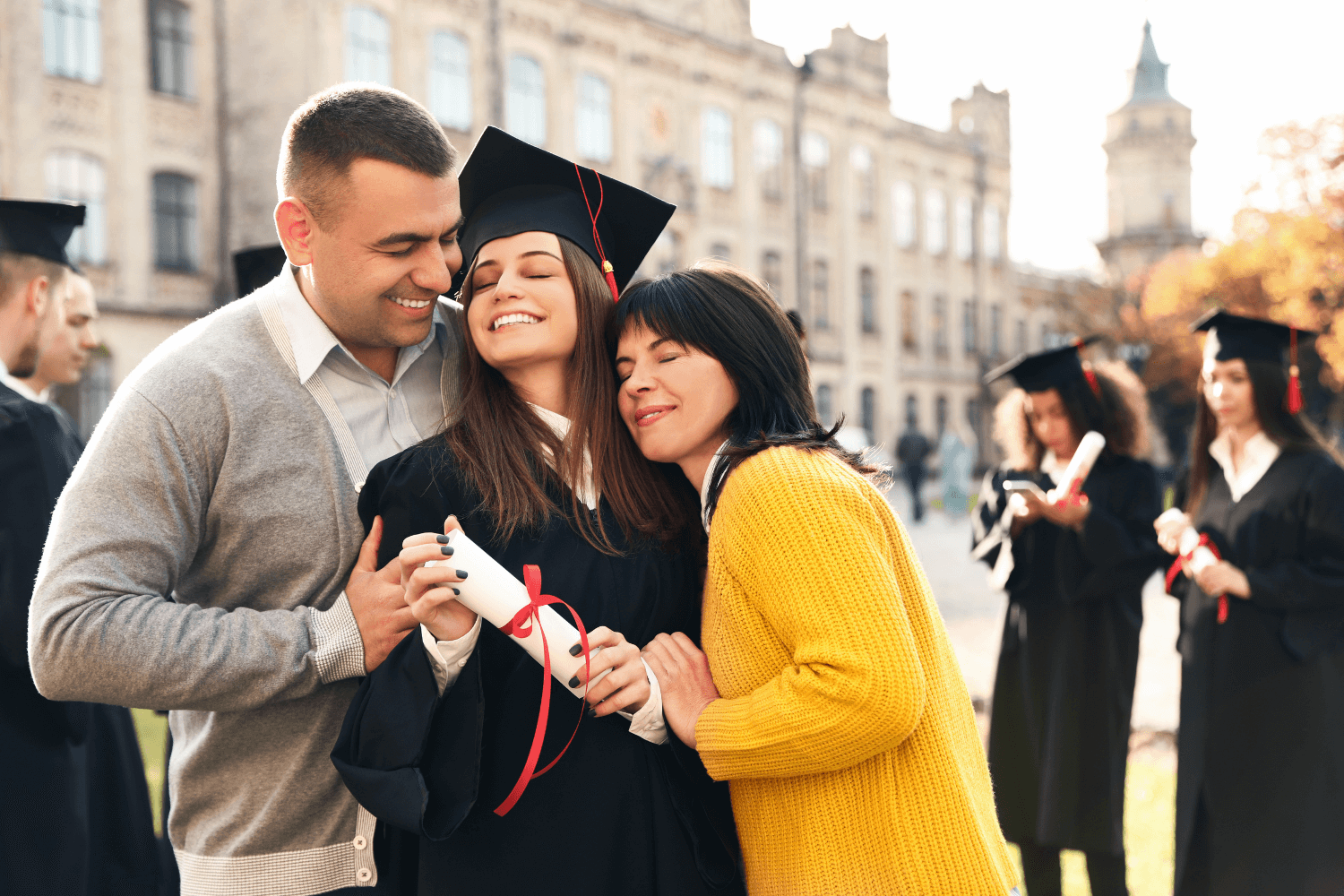 Parents hugging their daughter who just graduated college
