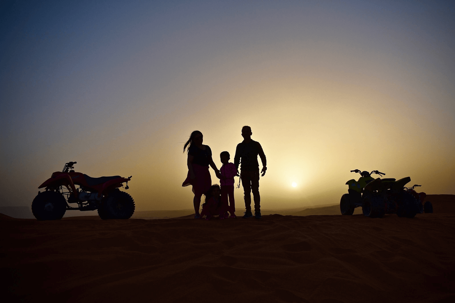 Family overlooking a sunset next to two four wheelers