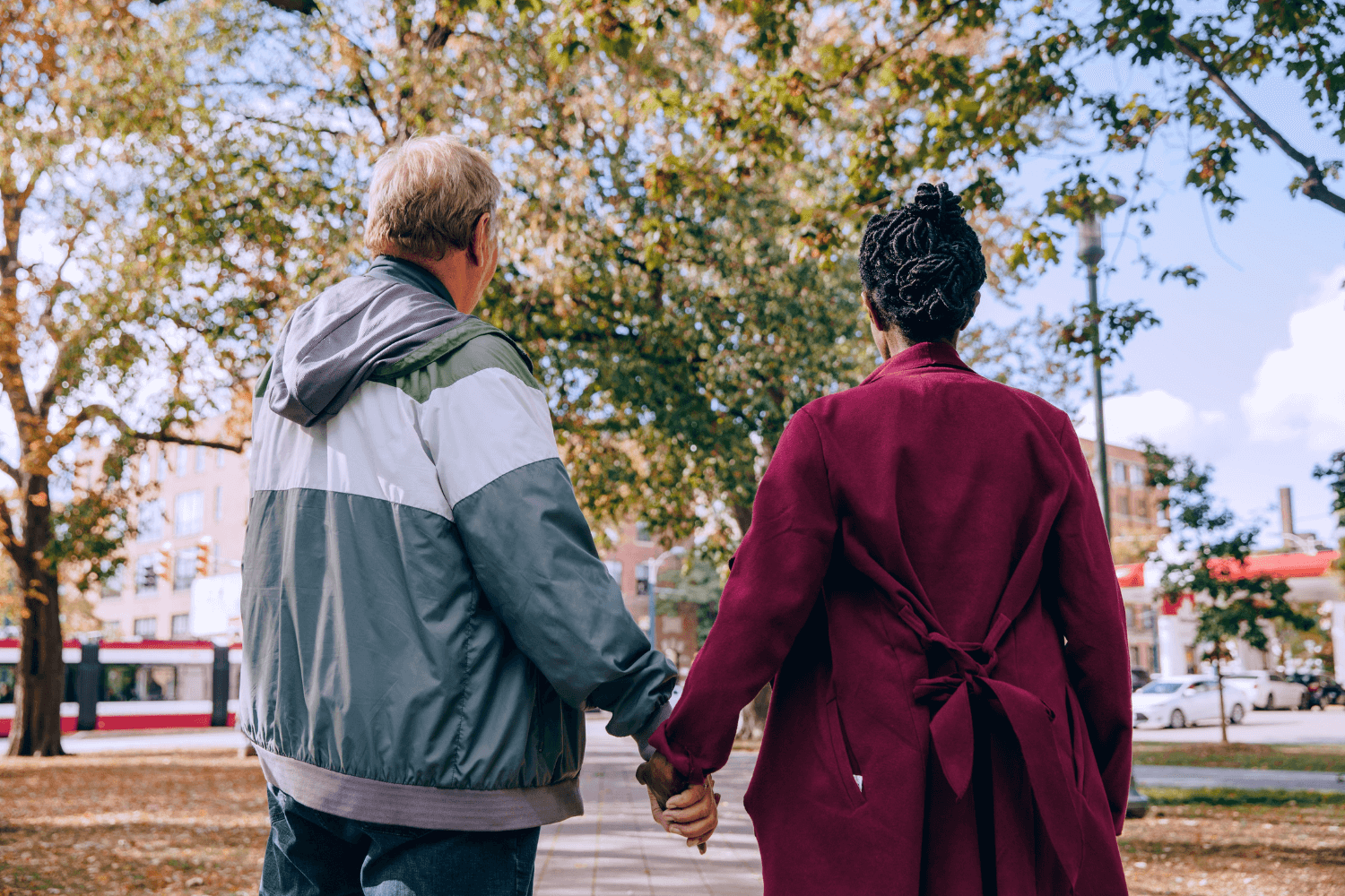 Older couple holding hands while walking through the park