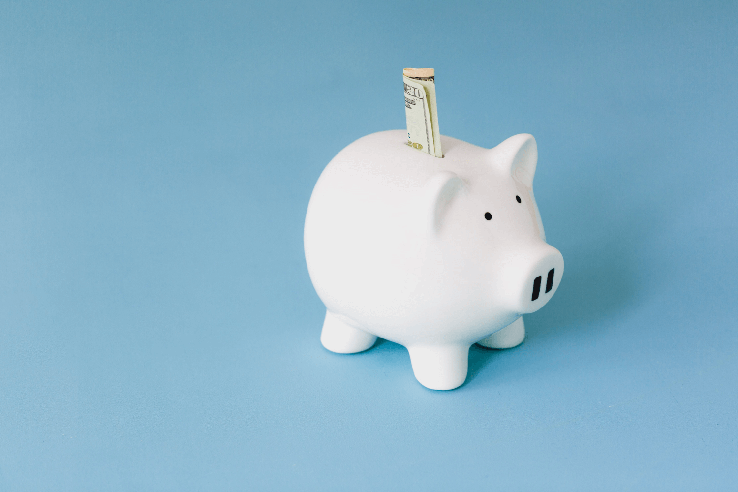 A piggy bank with money sticking out of it on a blue background