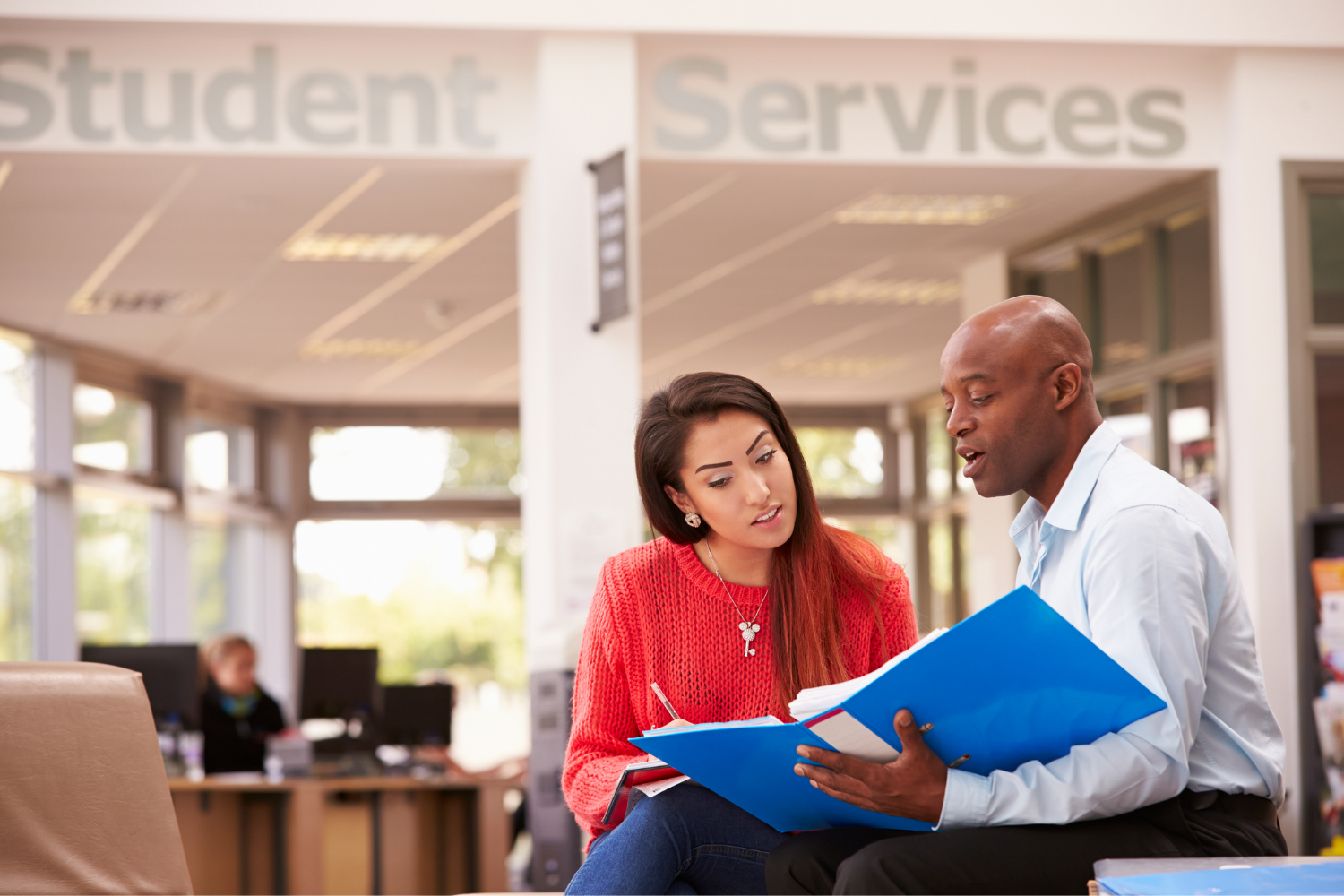 two people siting looking at a binder in a section labeled student services