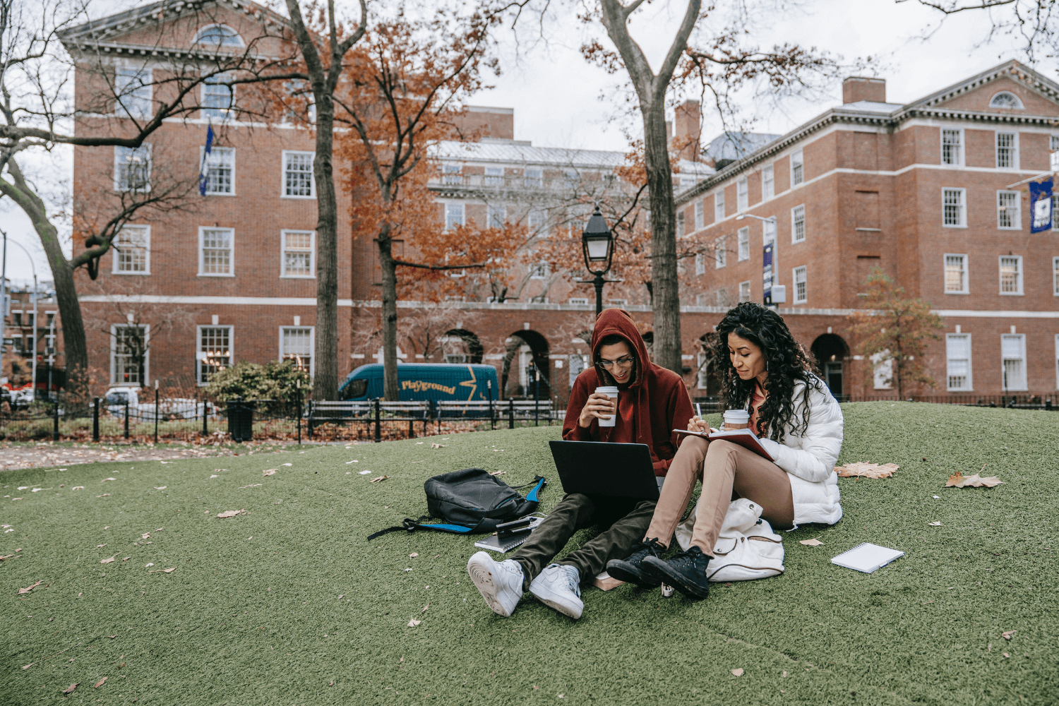 Two students sitting on a lawn comparing notes