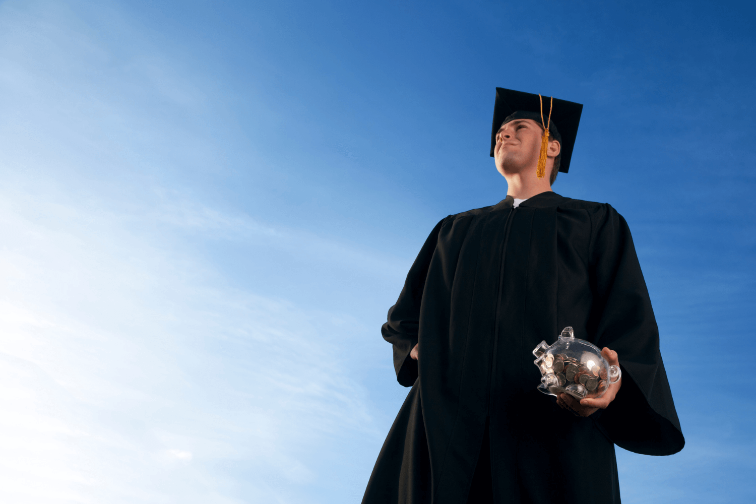 College graduate holding a transparent piggy bank with a bright blue sky in the background