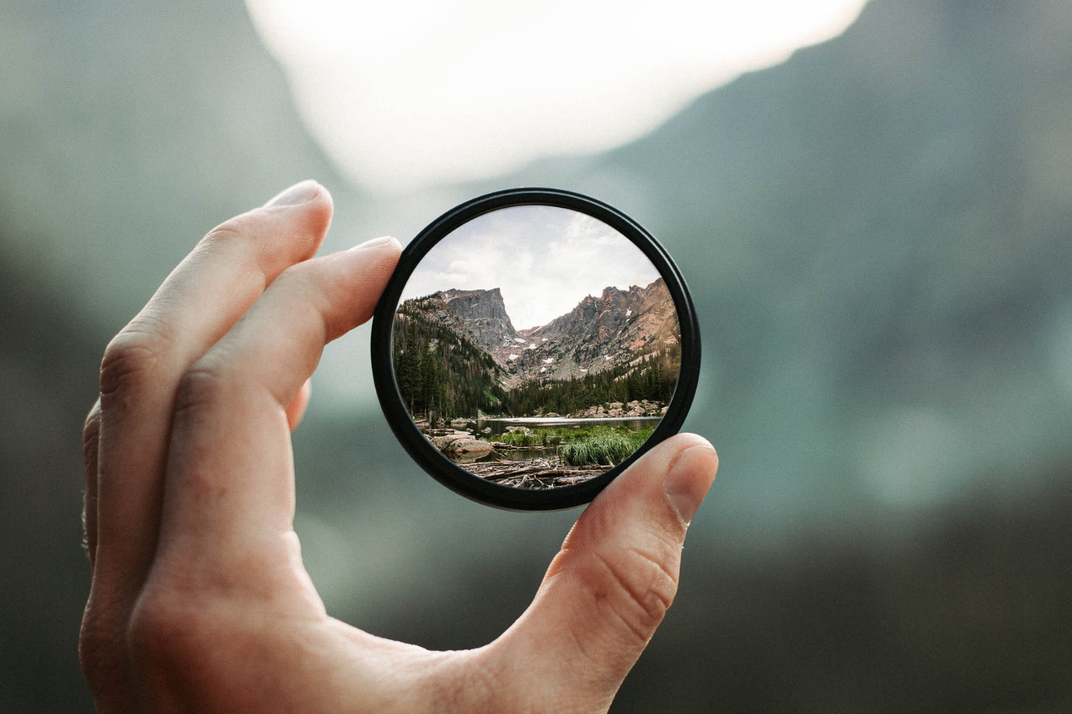 Lens being held by hand that focuses on mountains