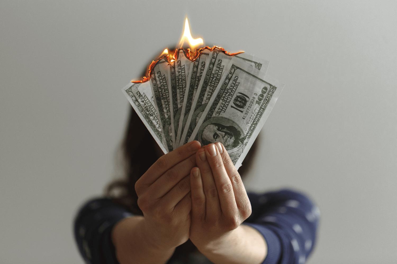 Money burning symbolizing old money beliefs