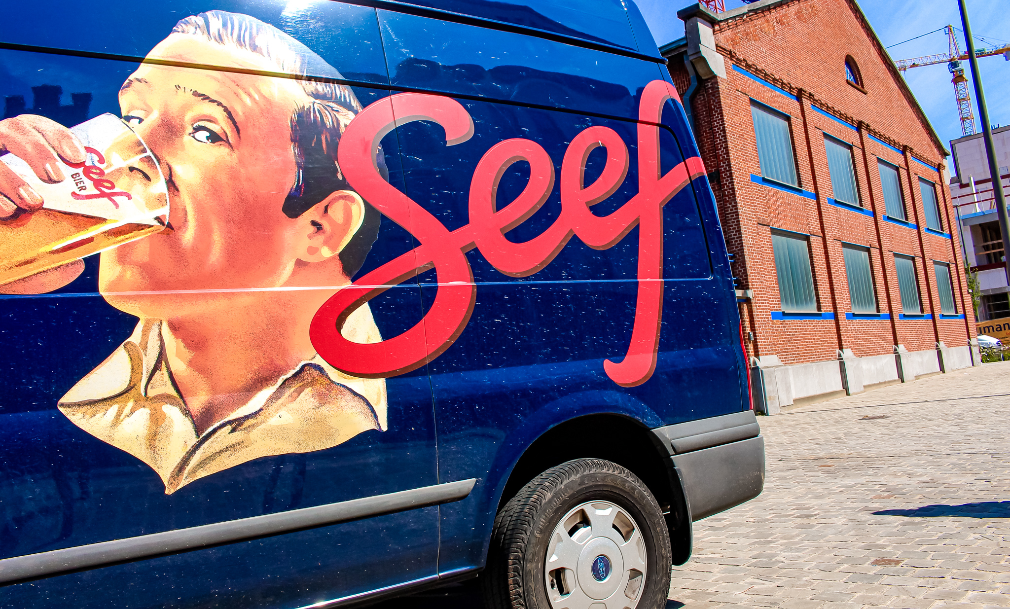 "Blue van with a man drinking beer labelled ""Seef"". Behind the van is the Seef Brewery in Antwerpen"