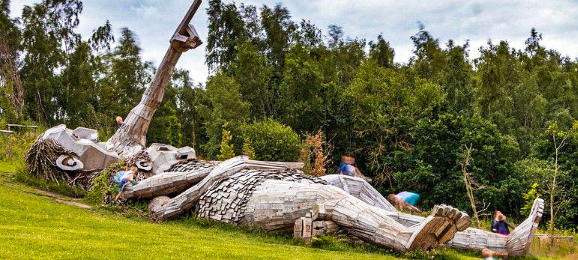 Two wooden troll sculptures lying down on the grass in De Schorre park, Antwerp