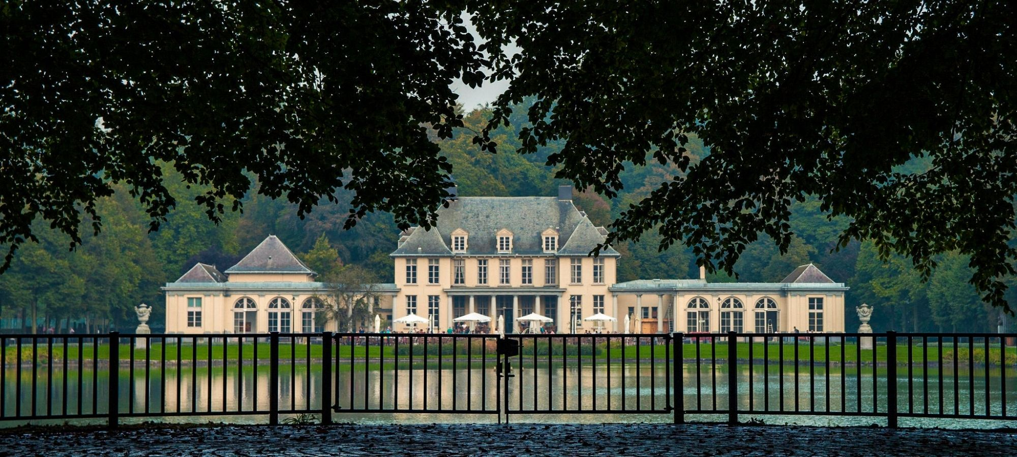 18th century Rivierenhof castle, in Classicism style, stands behind a black fence and wide pond