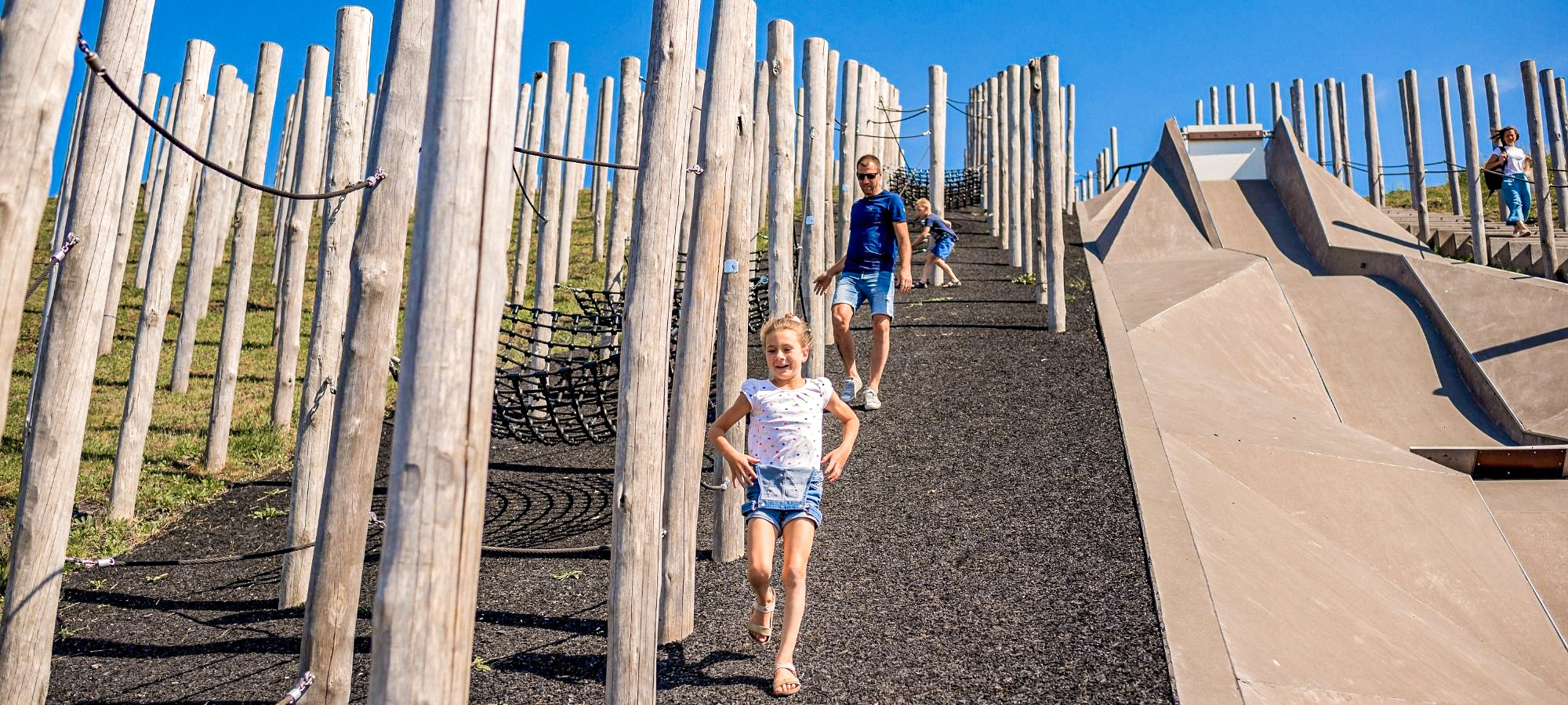 Two children and a man run down an asphalt covered slope surrounded by wooden poles with blue sky in the background.